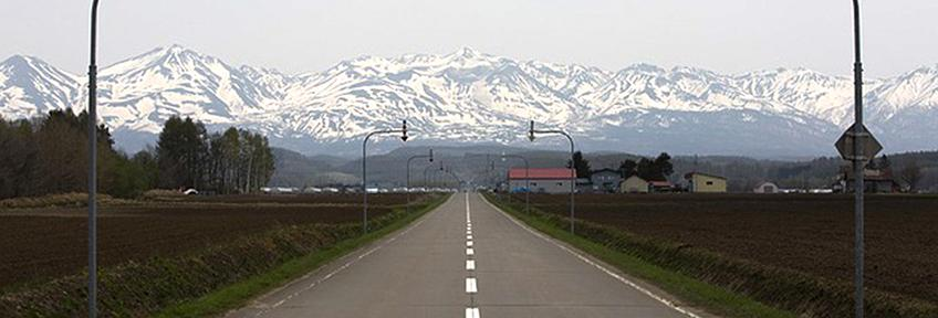 An empty road heading straight to the mountains of Hokkaido, Japan