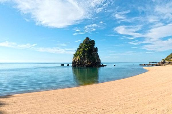 A small island, sky and the seas meet at the sands of Abel Tasman National Park in New Zealand