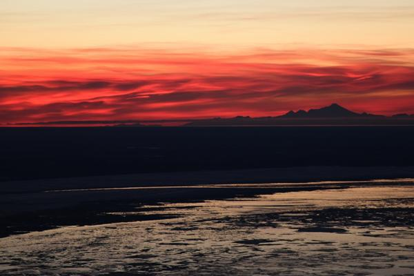 The setting sun turns the clouds red just before night near Anchorage, Alaska