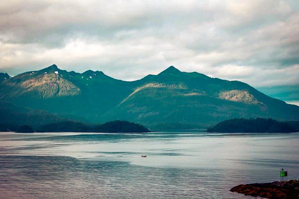 Distant view of a fisherman's boat on the water with a mountainous backdrop in Alaska