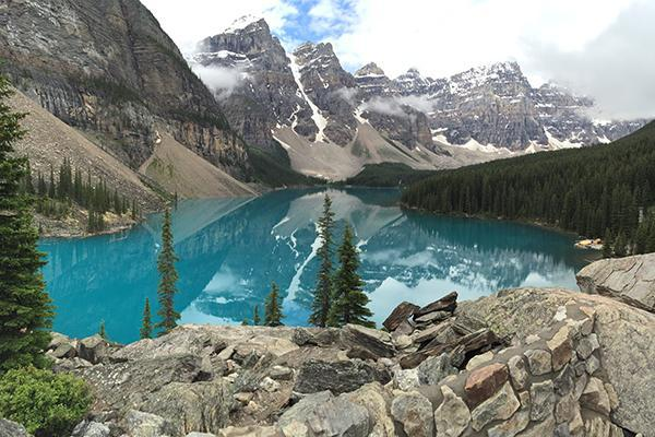An emerald blue lake surrounded by lush greenery and the snow capped Rocky Mountains in Alberta, Canada