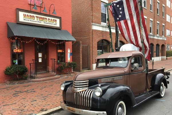 A vintage pick-up truck sits outside of a cafe in Alexandria, Virginia