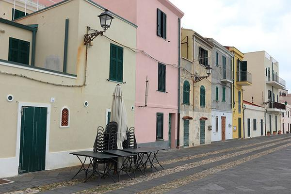 Colourful character buildings line a sea-facing road in Sardinia's Alghero