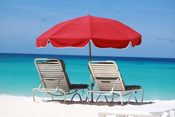 Two chairs sit under a beach umbrella on a stunning day in tropical Anguilla