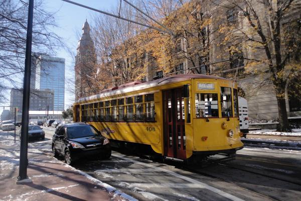 Snow melts on the ground as the River Rail Streetcar glides through the streets of Little Rock, Arkansas