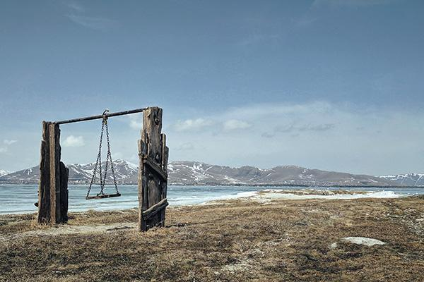 A wooden swing stands next to a beautiful water and mountain landscape in Chkalovka, Armenia