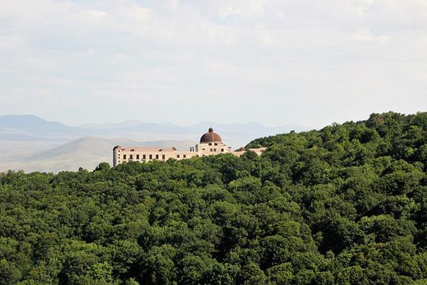A hotel stands above thick trees in the countryside near Tsaghkadzor, Armenia