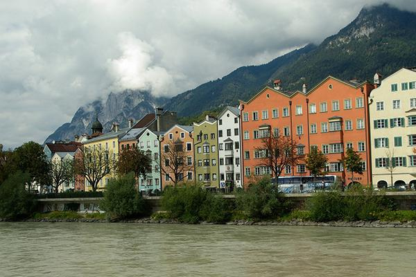 Colourful buildings lined up in front of the Inn River with a mountain backdrop in Innsbruck, Austria