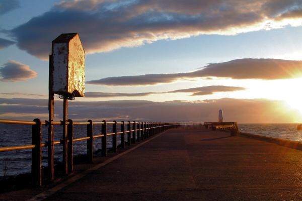 The sun sets on an oceanside pier in Ayrshire, Scotland