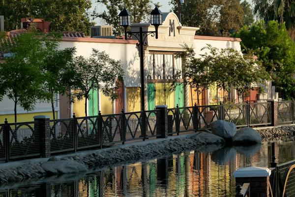 A colourful house reflects off of the waters of a canal in Bakersfield, California