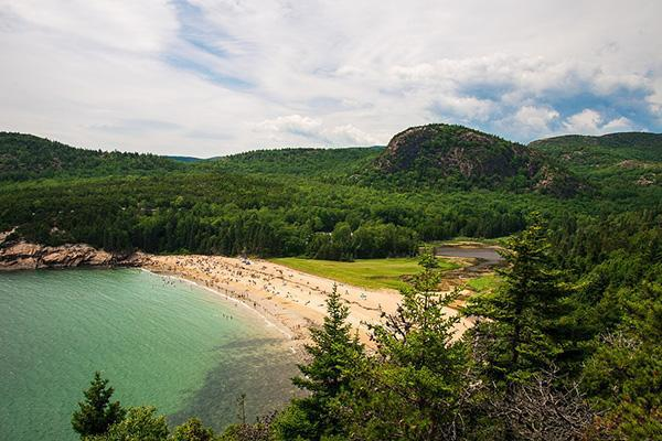 Sunseekers gather on the tree-lined beach at Acadia National Park in Bar Harbor, Maine