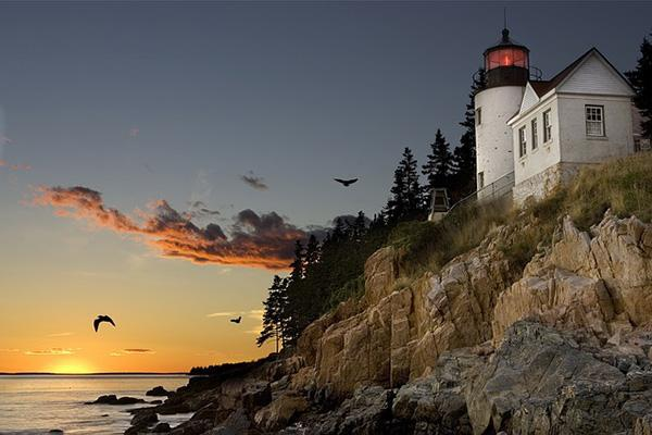 A cliffside lighthouse overlooks the sea at sunset in Bar Harbor, Maine
