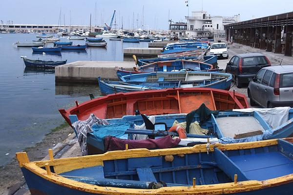 Small, colourful fishing boats line the port in Bari, Italy