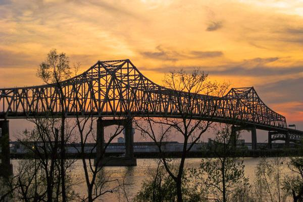 The Horace Wilkinson Bridge stretches over the Mississippi River at sunset in Baton Rouge, Louisiana