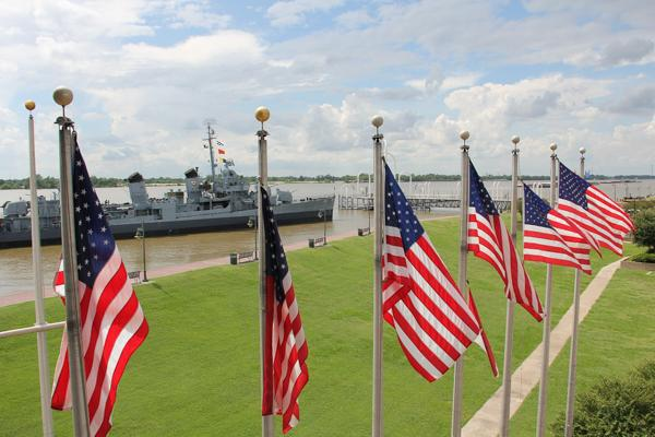American flags wave in the wind in front of a naval battleship in Baton Rouge, Louisiana