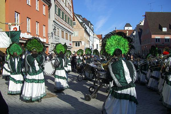 A band dressed in costume plays music and marches along the streets of Memmingen, Germany