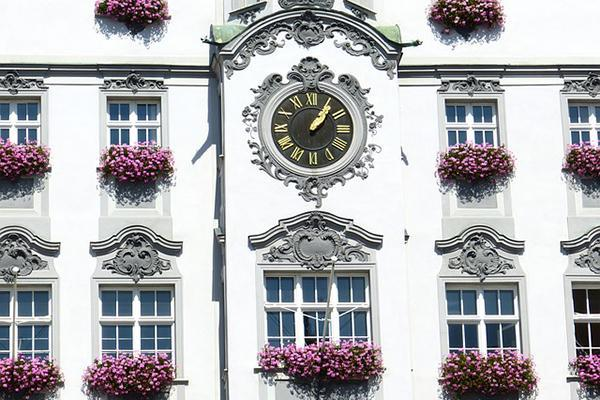 A clock, surrounded by windows with fresh flowers are on the façade of a white, beautiful building in Memmingen, Germany