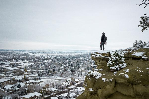 A hiker stands at Zimmerman Park overlooking Billings, Montana in winter