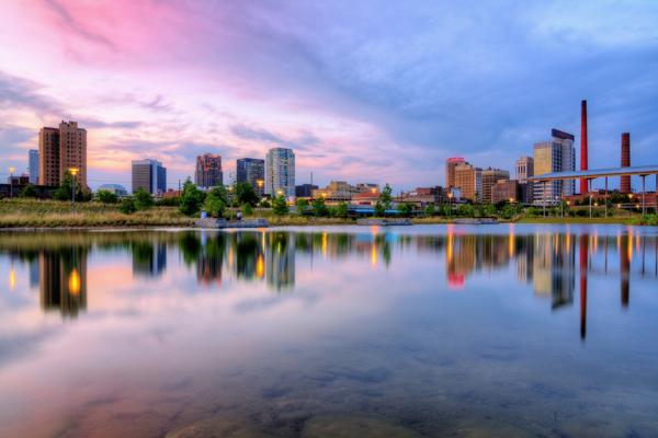 Downtown Birmingham, Alabama reflects off the tranquil waters during sunset