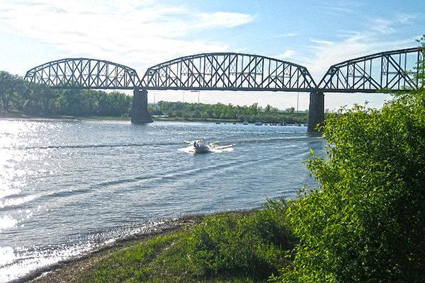 A boat speeds across the Missouri River in front of The Northern Pacific (BNSF) Railway Bridge in Bismarck, North Dakota