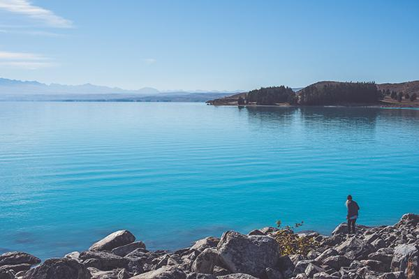 The vivid blue waters of Lake Pukaki shine in the midday sun in New Zealand