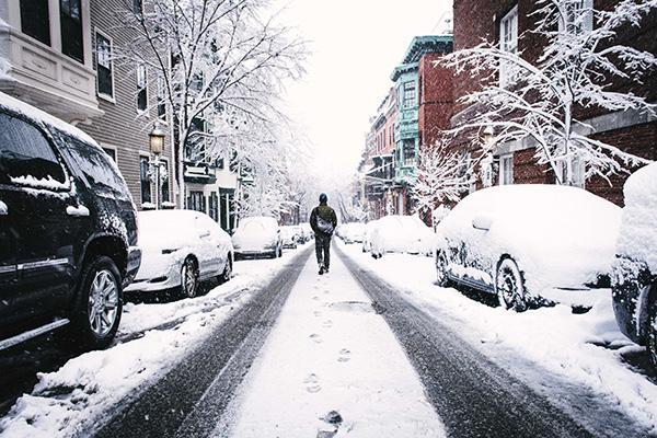 A man walks down a snow-covered lane in downtown Boston
