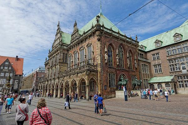 People go about their business near the ornate Bremen Town Hall in Bremen, Germany