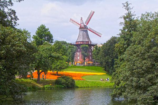 A historical windmill amongst trees and flowers in Bremen, Germany