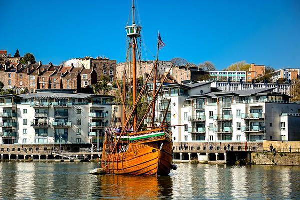An old wooden ship glides across Bristol Harbour, with the cityscape as a background