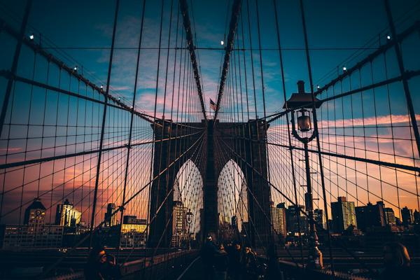 The sun sets over the Brooklyn Bridge in downtown New York City, New York