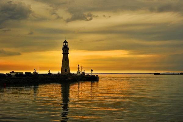The sun sets behind a lighthouse on Lake Erie in Buffalo, New York