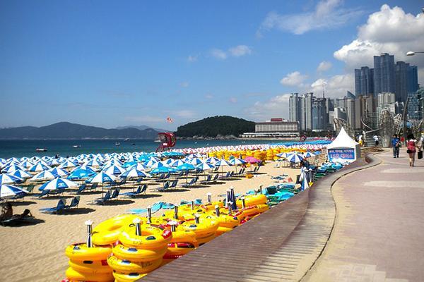 Sun umbrellas and rafts line the beach next to the boardwalk at Haeundae Beach in Busan, South Korea