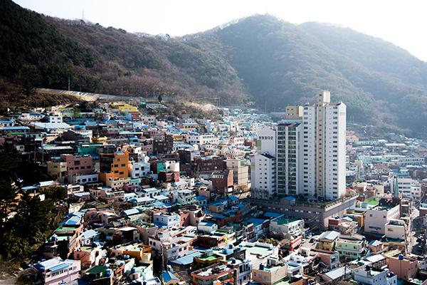 Colourful houses and one plain apartment building fill the hills of Busan, South Korea