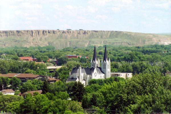 A church sits in the valley of the mountains surrounded by trees in Medicine Hat, Canada