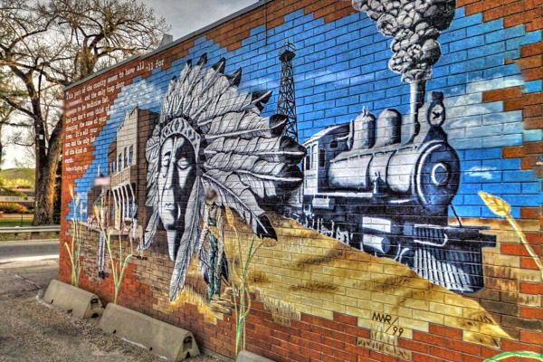 A brick wall covered in artistic imagery relevant to the native roots of Medicine Hat, Canada