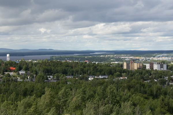 A lake and forest of trees surrounds the city of Val-d'Or, Canada