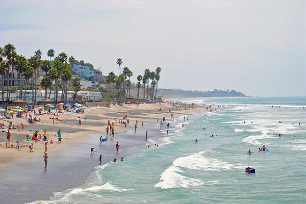 Beachgoers having seaside fun in Carlsbad, California