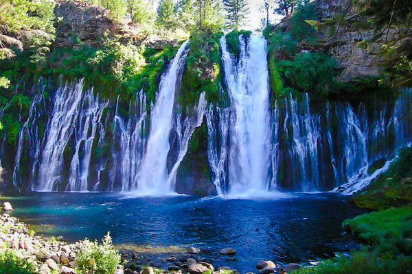 Shimmering water cascades down tree-lined Burney Falls in California
