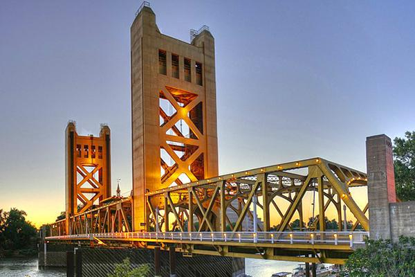 View of the lit up Tower Bridge at sunset in downtown Sacramento, California