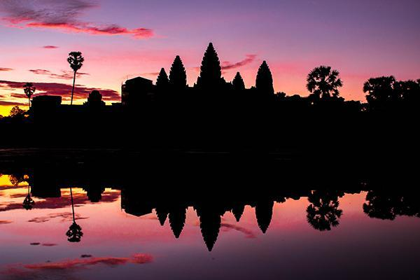 Angkor Wat reflects off the water at sunset in Siem Reap, Cambodia