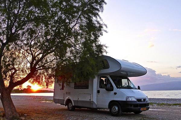 A self-contained motorhome next to a beautiful lake at sunset