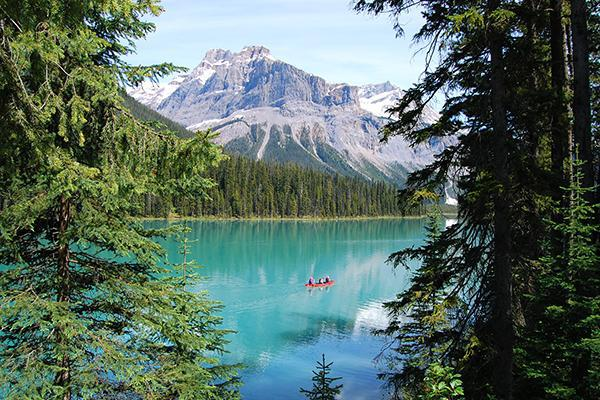 Three people paddle a red canoe in Emerald Lake, Canada