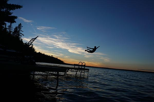 A man jumps off a dock into the water at sunset in Canada