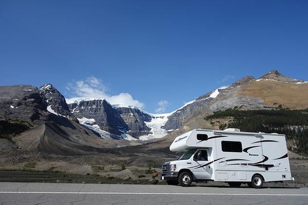 A motorhome parked on the highway beside snow-capped mountains in Canada