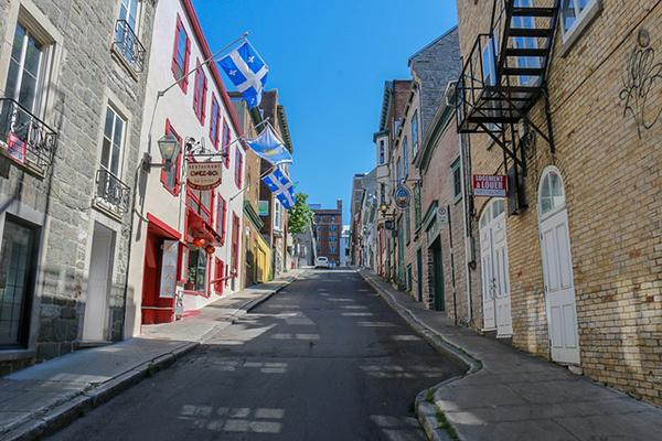A quaint, quiet street with beautiful buildings and provincial flags in Quebec City, Canada