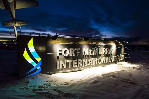 The Fort McMurray International Airport sign lit up in winter in Alberta, Canada