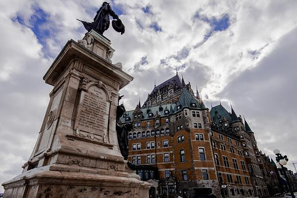 A statue stands in front of the grand Château Frontenac in Old Quebec, Canada