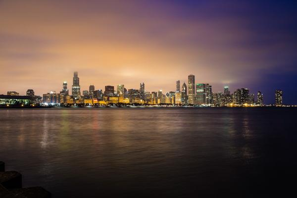 The bright city lights reflect off of the water in the city of Chicago, Illinois