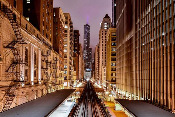 Lights illuminate the train tracks which cut through the buildings leading downtown in Chicago, Illinois