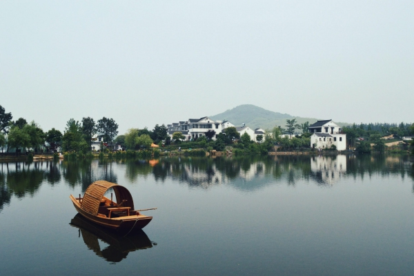 A wooden boat floats on calm, still waters in front of the hilly countryside of Nanjing, China